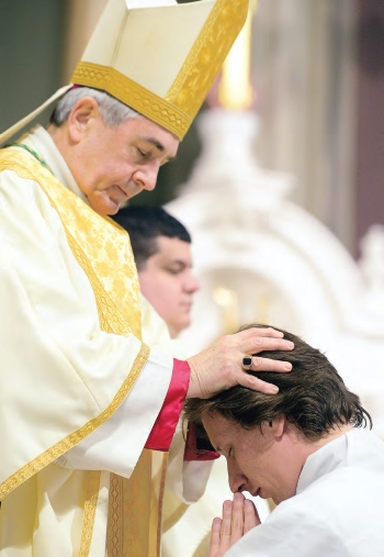 Bishop Ronald Gainer lays his hands on the head of Deacon Kenneth Roth. It is through the imposition of hands, and the consecratory prayer that follows, that the men were ordained deacons.