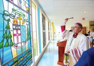 Bishop Ronald Gainer blesses the memorial window to Father Louis Ogden, who served on the Board of Directors at Bishop McDevitt High School for 17 years.