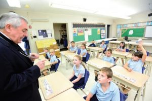 Bishop Ronald Gainer explains the meaning of his pectoral cross to second-graders at Our Mother of Perpetual Help School in Ephrata.