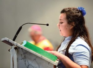 Sixth-grader Julie Leonard serves as the lector during the school's 60th anniversary Mass.