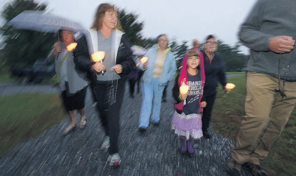 Luminaries light the way during the procession on the church grounds.