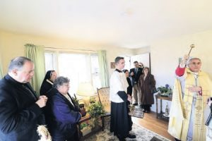 Bishop Ronald Gainer blesses the new convent at St. Joan of Arc Parish in Hershey as Father Al Sceski, pastor, and the Daughters of Our Lady of Mercy look on.