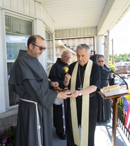 Father Michael Lasky, OFM Conv., Chair of the Franciscan Friars' Justice, Peace & Integrity of Creation ministry, holds a crucifix that Bishop Ronald Gainer blesses at the Franciscan Center in Coal Township on Memorial Day.