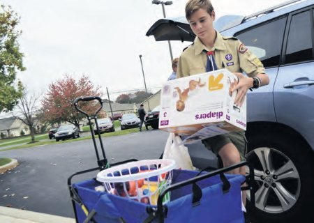 Jacob Beeghley unloads items gathered for Lourdeshouse Maternity Home from a wrestling clinic conducted for his Eagle Scout Project.