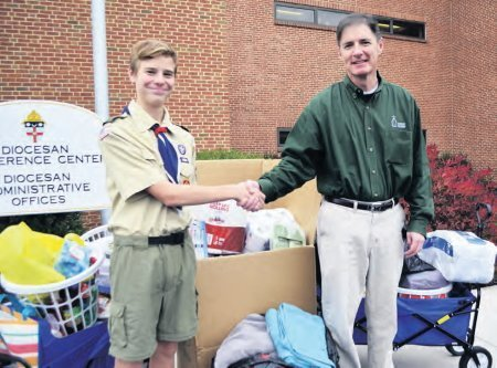 Jacob Beeghley of Troop 23 from St. Catherine Labouré Parish in Harrisburg presents a collection of cleaning supplies and toiletries to Christopher Meehan, Director of Development for Catholic Charities.