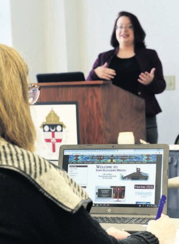 Sally Lanza of St. Katharine Drexel Parish in Mechanicsburg takes notes as Rachel Bryson, M.S., Diocesan Executive Director of Public Relations, presents tips on website appearance and layout.