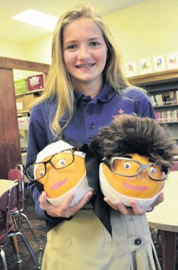 Jade Kent displays her Pennies for Life contest pumpkins, Sister Gertrude and Father Milton, who graced the McSherrystown Campus.