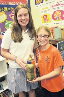 Kat Keller and Ella Staub hold the Pennies for Life baby bottle trophy, created by the Student Council. This year's trophy went to the seventh grade class for raising the most money.