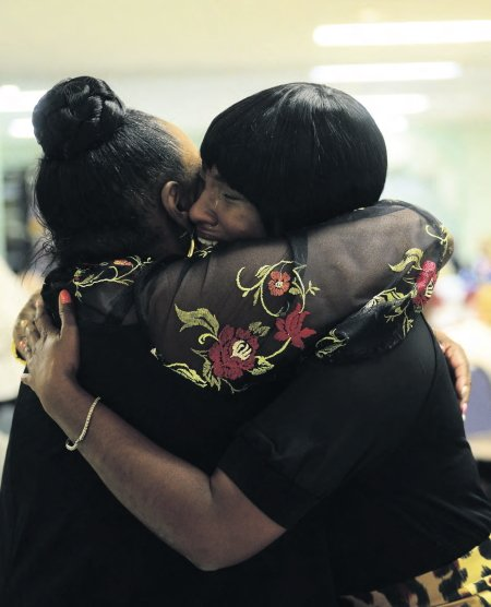 Rashanda Lloyd shares a tearful embrace after speaking of the help and hope she found at Lourdeshouse maternity home. Lloyd spoke at this year's Come and See dinner to benefit Catholic Charities' residential programs.