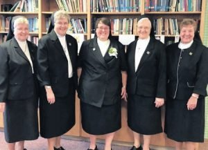 Sister Mary Kate, SSCM, center, a 2003 graduate of Our Lady of Lourdes Regional School, professed her first vows on Sept. 14. She is pictured with Sisters Marcine, Pam, Agnes Marie, and Canice.