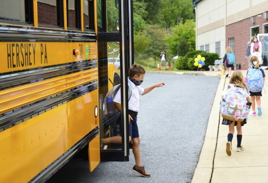 Brandon Dodd steps off the bus and follows his sister Annagrace to the first day of school.