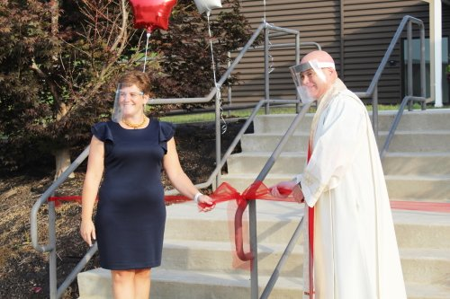Kyla Hockley, principal, and Father Daniel F.X. Powell, executive pastor, cut the ribbon at the new St. John Neumann Catholic School in Lancaster Sept. 8.