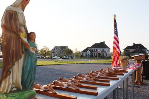 Crucifixes and American flags that will hang in each classroom are seeing prior to their blessing.